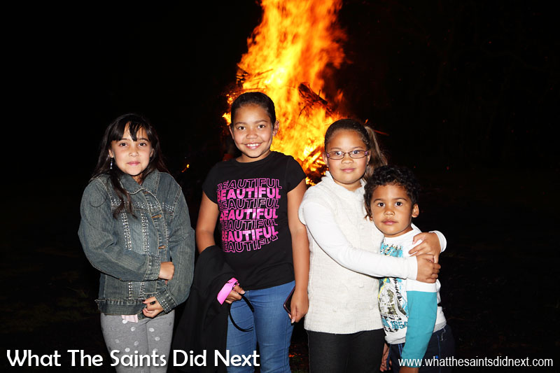 Happy group of school kids enjoying the bonfire and glad the rain has stopped for a bit. Bonfire night in Sandy Bay, St Helena Island.