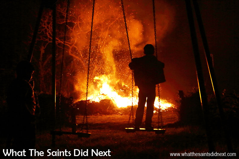 A young boy on the nearby swings watches on as the fire finally starts to die down. Sandy Bay, St Helena Guy Fawkes Day and Bonfire Night.