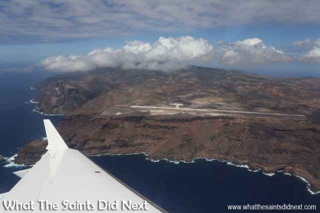 A stunning view of St Helena and the airport on Prosperous Bay Plain, moments after take-off. The cluster of clouds have formed over the island's central peaks. Flying from St Helena Airport.