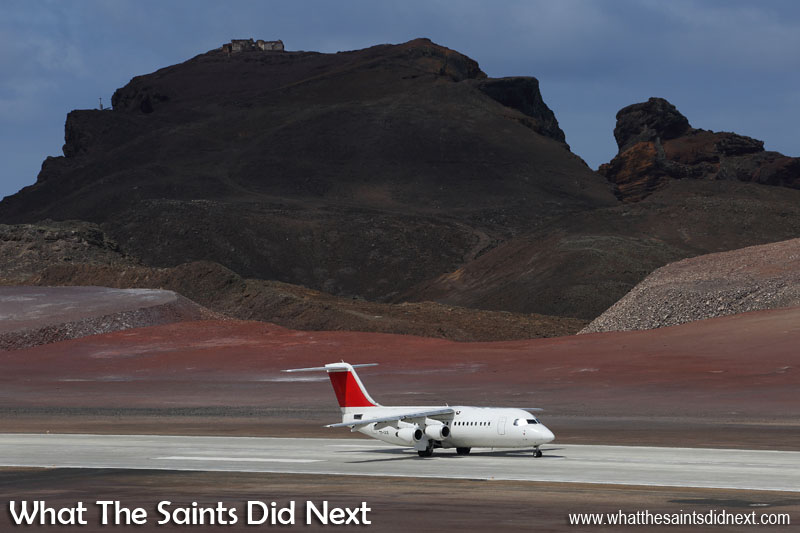 The Atlantic Star/Tronos, Avro RJ100 taking off from St Helena Airport, against the rising landmark of Prosperous Bay House.