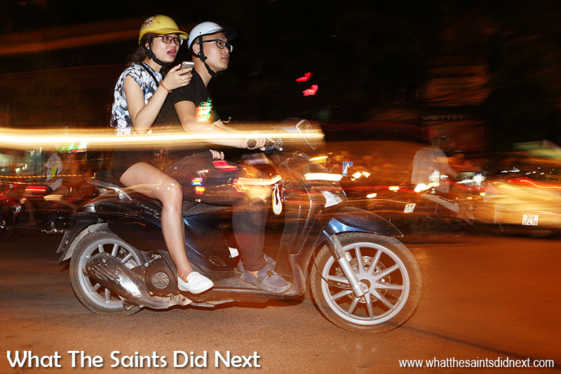 Street photography tips - dragging the shutter for cool effects of mopeds at night in Hanoi.