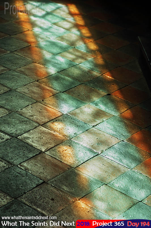 Stained glass window light reflecting on floor tiles.