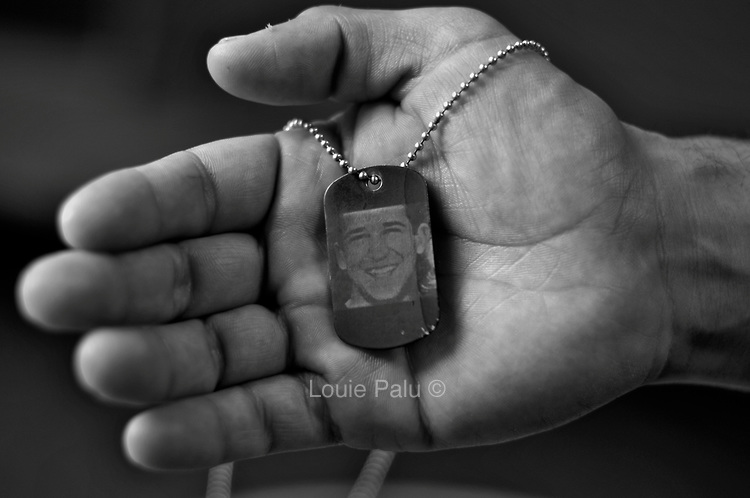Michael Kacer age 27 from Scranton, Pennsylvania holds a dog tag with a picture of his friend Medic Marc Retmier, age 19 who was killed in Afghanistan in 2008..Photo by ©Louie Palu