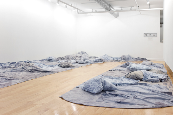 """Installation shot of """"Flight, 2014"""", photographically printed blankets and pillows by Judy Haberl (courtesy of the artist and Gallery Kayafas, Boston)"""