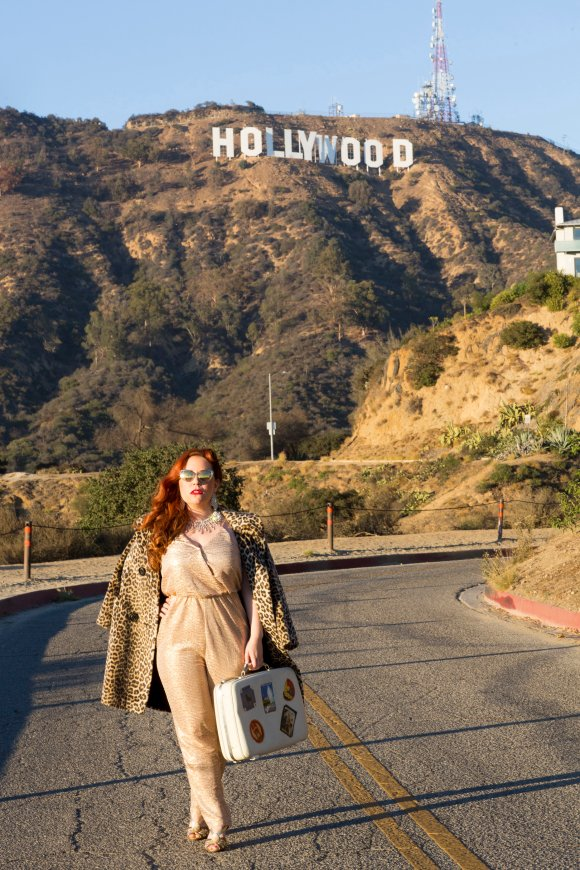 With the style of a movie diva, Nicole walks confident with her inseparable traveling case. Location: Hollywood sign, Los Angeles Hair and makeup: Ori Brown Vintage coat: Vintage by Misty Sunglasses: Tom Ford Gold pants suit: Nordstrom Photographer: Andrea Miner for Flytographer