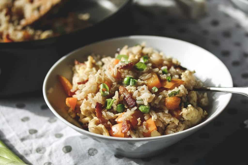 a white bowl with bacon fried rice