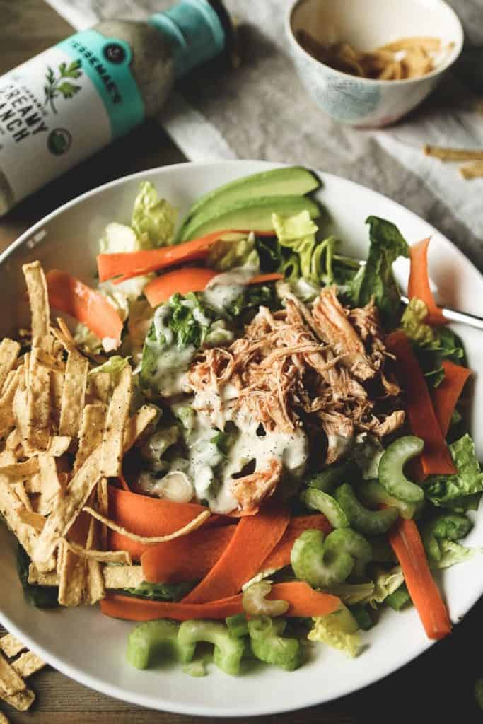 a bowl full of salad with celery, green onion, carrots, shredded buffalo chicken and ranch dressing