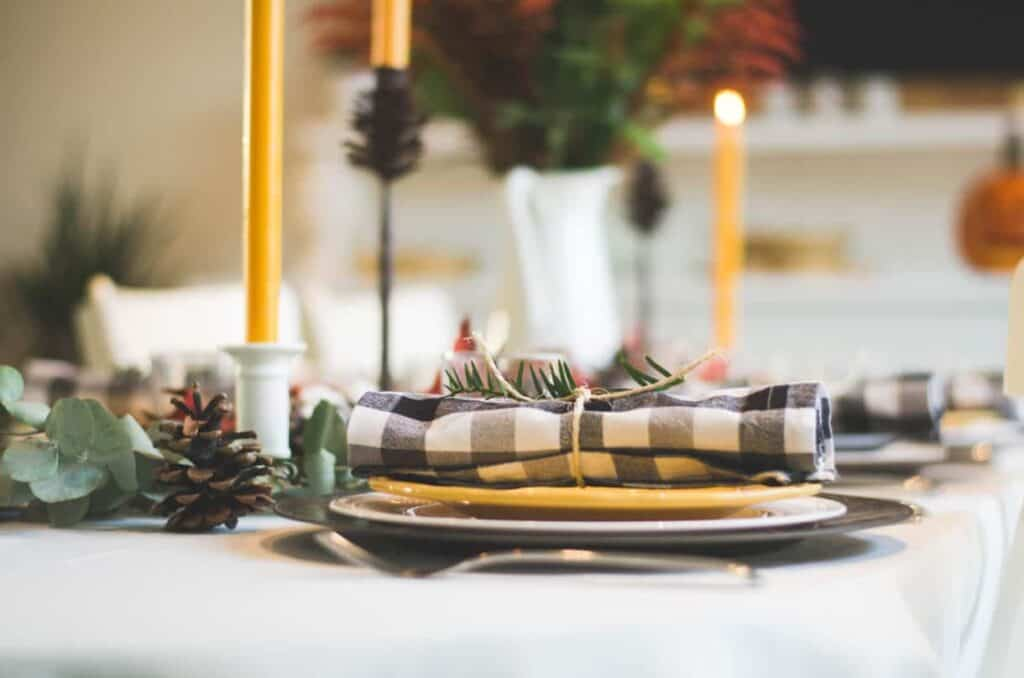 Photo by Libby Penner on Unsplash. Black and yellow holiday tablescape with Jack-o-lantern.