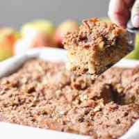 Apple cake in a parchment lined pan topped with pecans, a piece being lifted out with a spatula