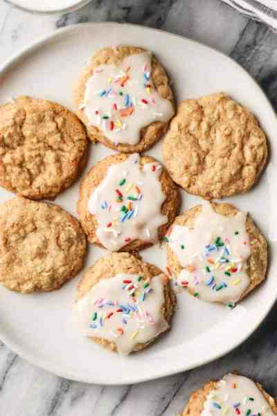 a plate of oatmeal cookies, some have icing and rainbow sprinkles