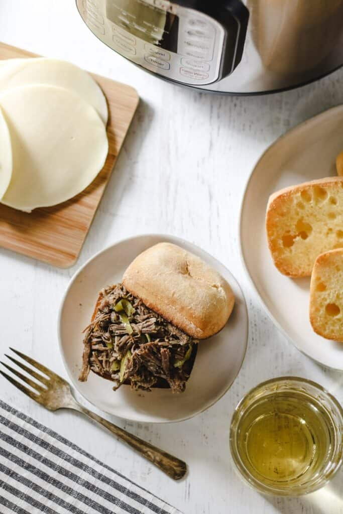 an Italian beef sandwich on a white plate near the instant pot, cheese and extra rolls on the side
