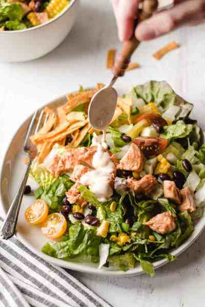 Pouring chipotle ranch dressing over a southwest bbq chicken salad piled high on a plate.