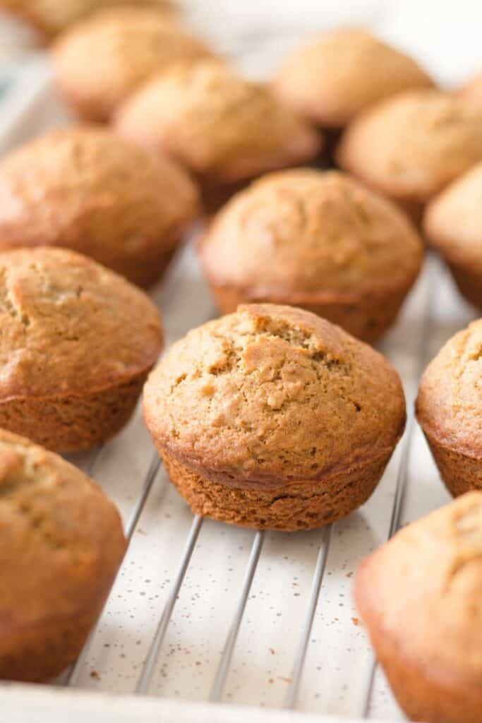 Gluten free whole grain banana muffins on a wire rack over a speckled baking sheet.