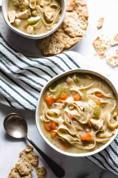Two bowls of chicken noodle soup with crackers.