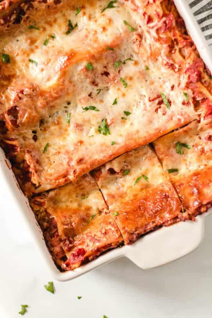 A pan of lasagna with three slices cut.