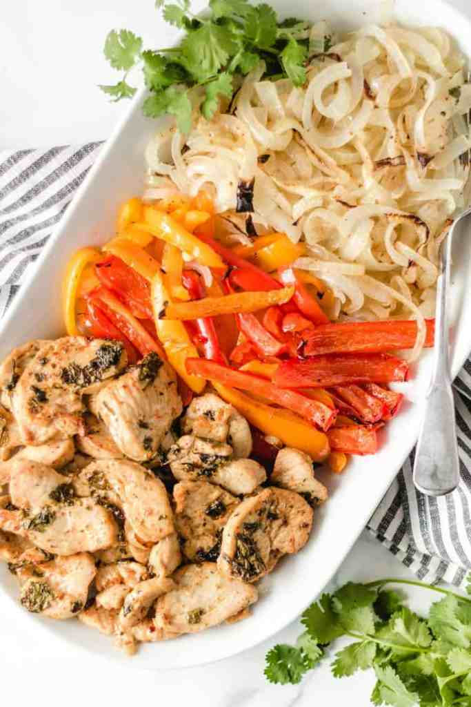 Cooked chicken fajitas on a white serving platter.