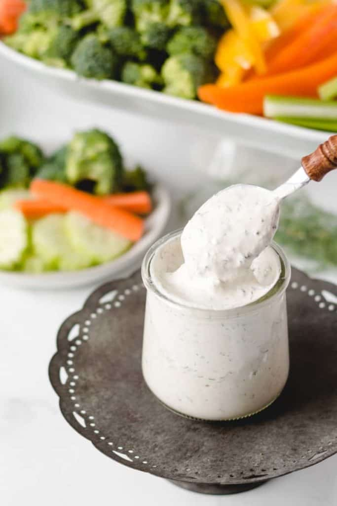 A spoon dipping into a jar of homemade ranch dip.