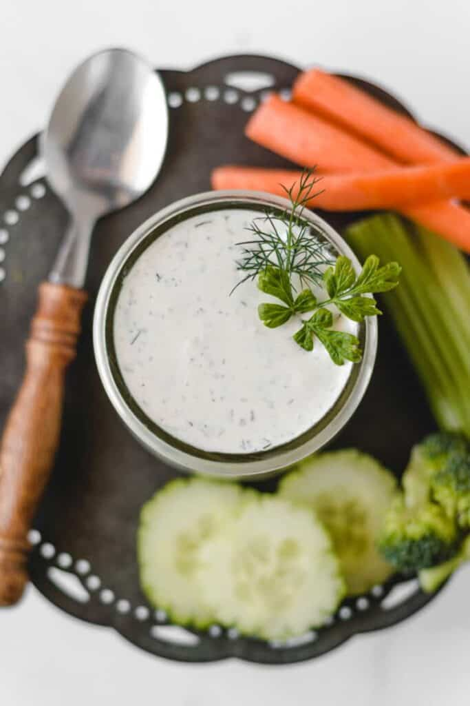A small glass jar with ranch dip and veggies in the background.
