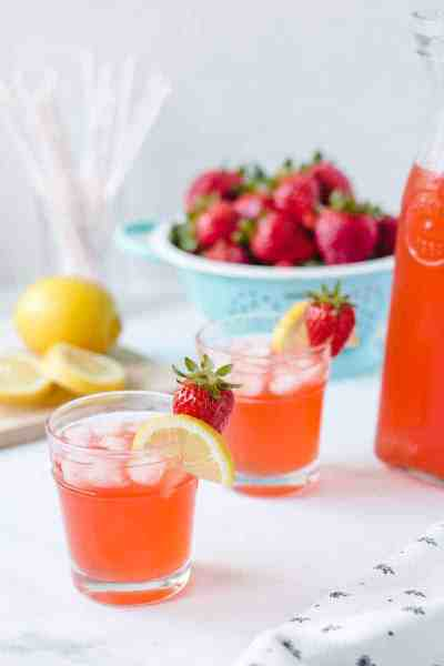 Two glasses of homemade strawberry lemonade with lemon and strawberry garnish.