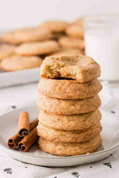 A stack of snickerdoodle cookies, gluten-free, next to cinnamon sticks and a glass of milk.