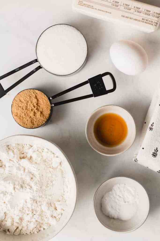 Ingredients needed for gluten-free snickerdoodles, gluten-free flour, egg, sugars, vanilla, and butter