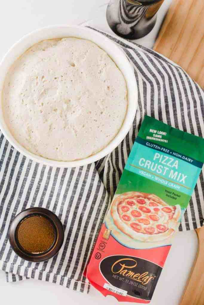 Pamela's Pizza Crust Mix next to a bowl of risen, bubbly pizza dough.