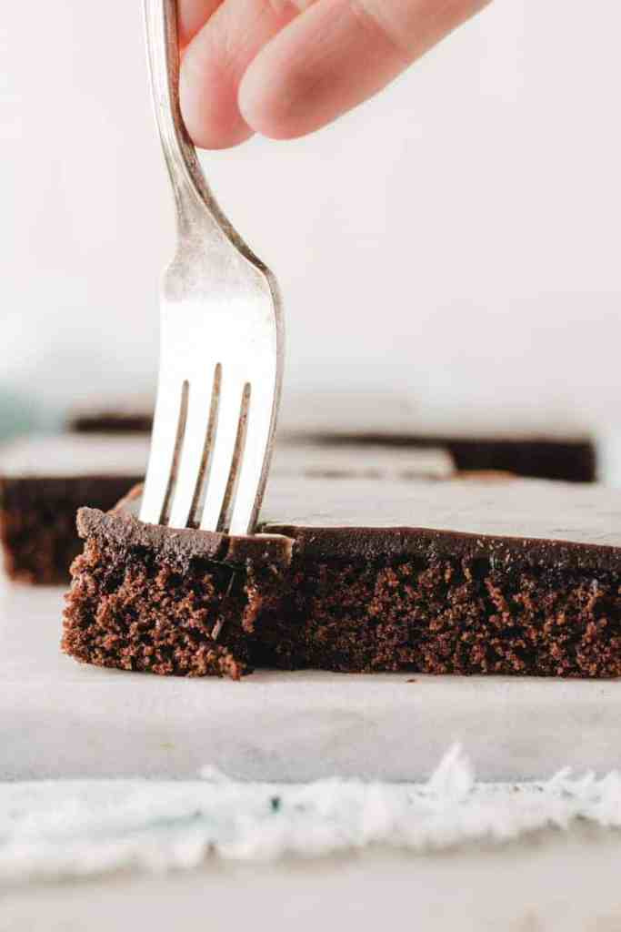 A fork sunk into corner of a slice of Texas sheet cake.