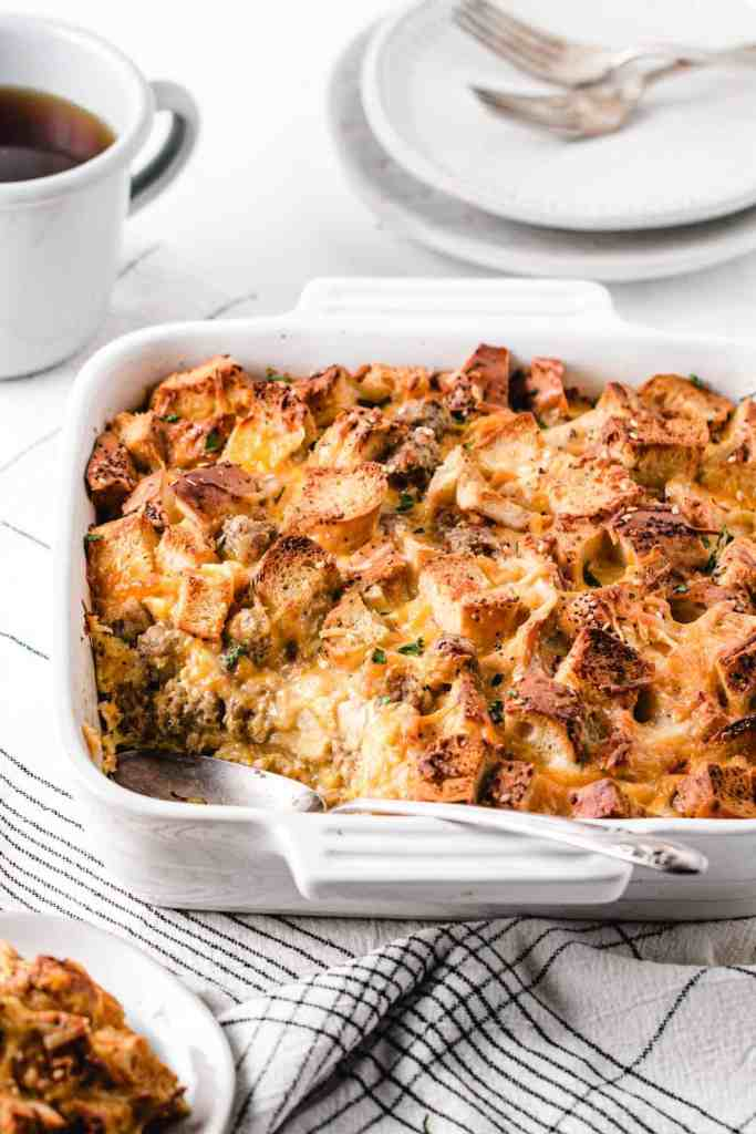 Crusty baked everything bagel strata in white baking dish with spoon resting in pan.