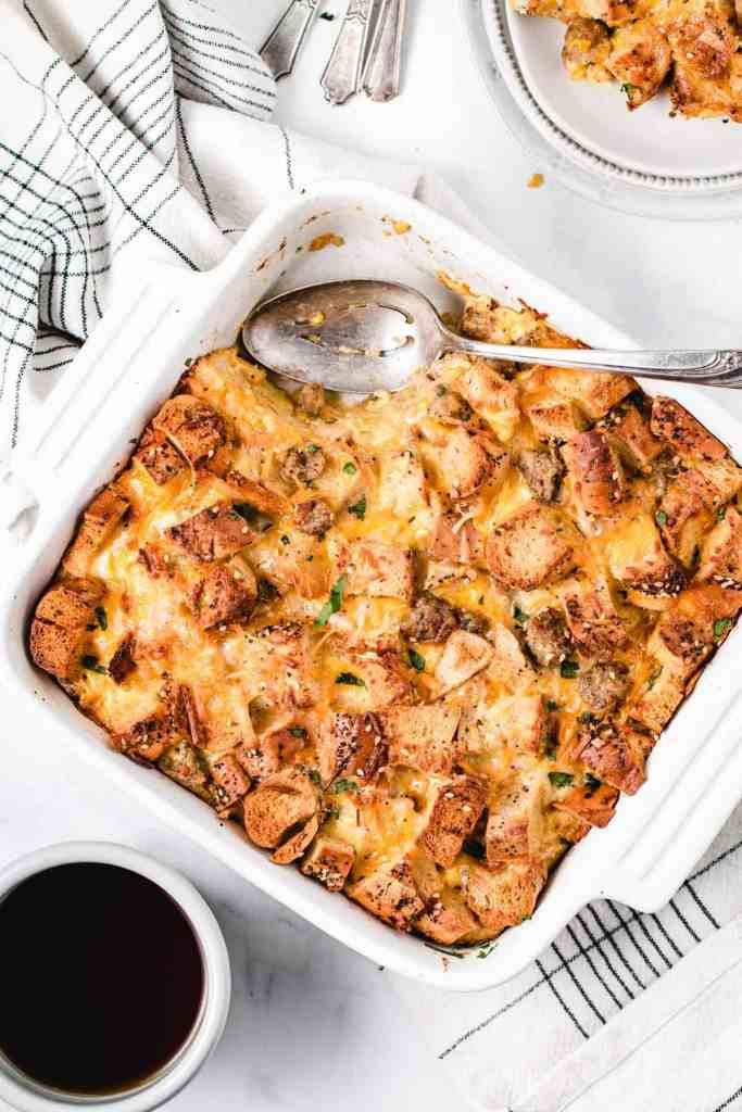 Gluten-free Everything Bagel Strata in a white square baking dish. It is brown and crispy on top with a scoop removed and spoon resting to the side.