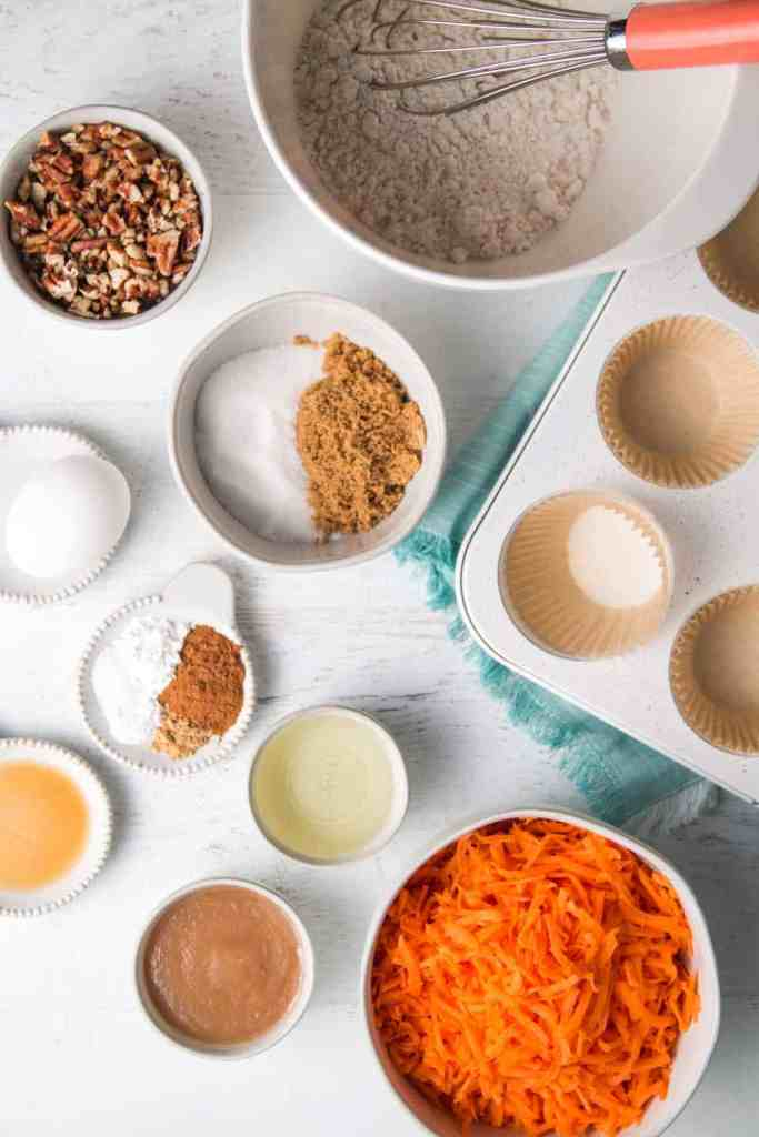 Ingredients for gluten-free carrot muffins measured in bowls. A whisk rests in the bowl of flour.