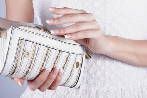 Beautiful female hands with manicure hold an open white handbag