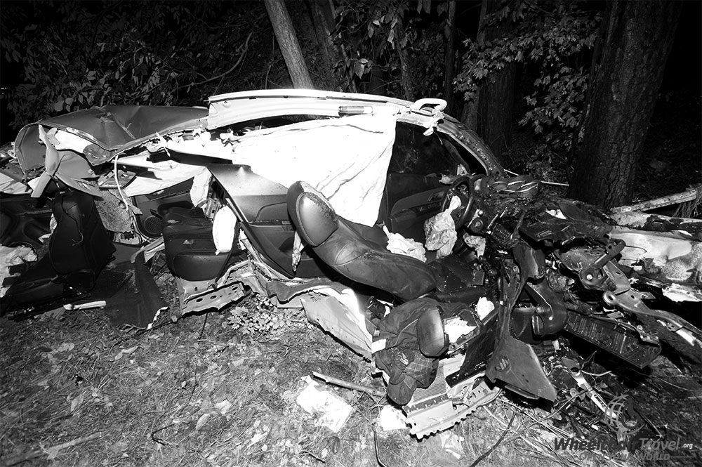 PHOTO DESCRIPTION: Crashed Chevrolet Cruz split in two, black and white image.
