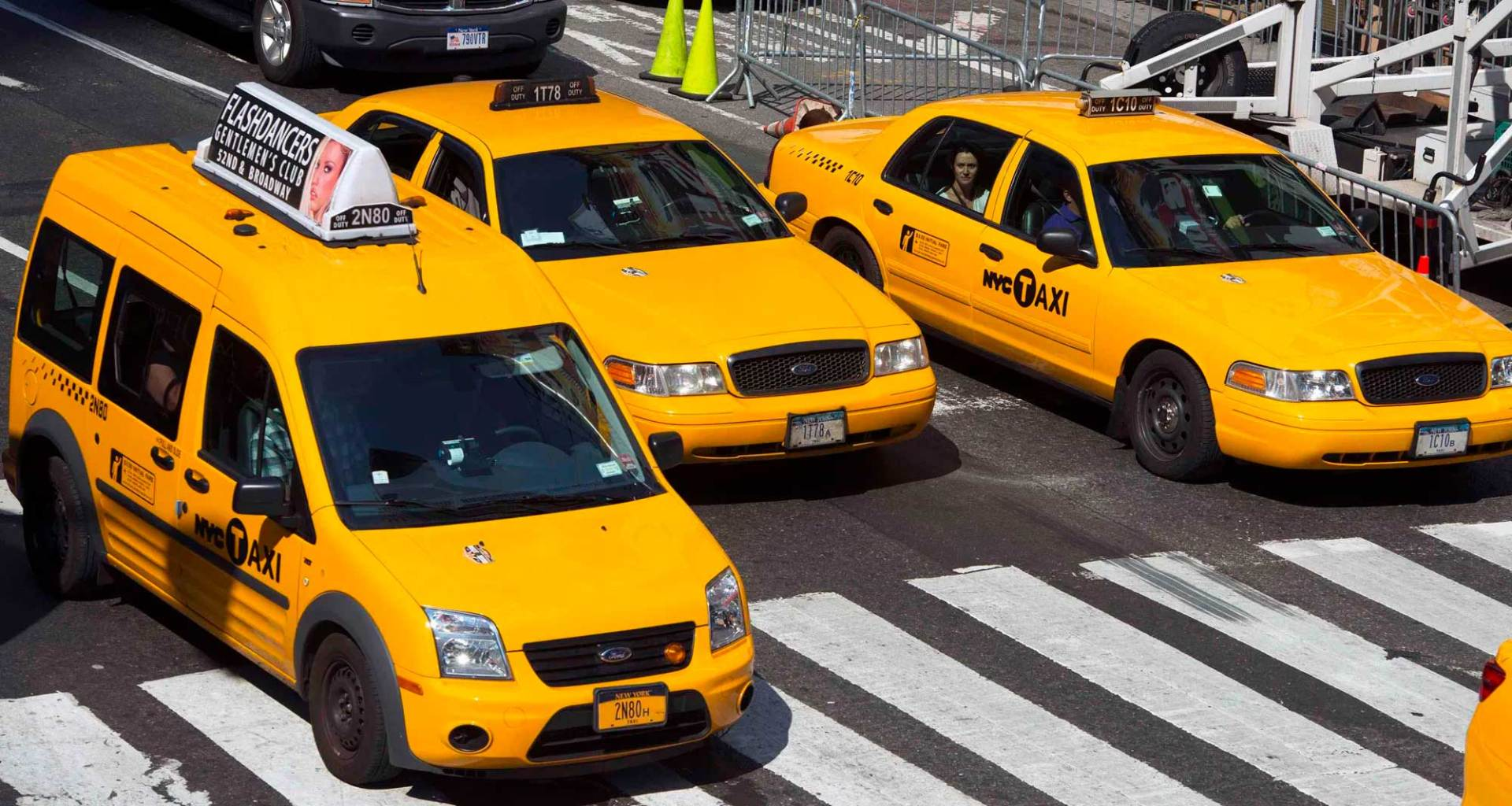 Three taxis stopped on the street at an intersection and crosswalk.