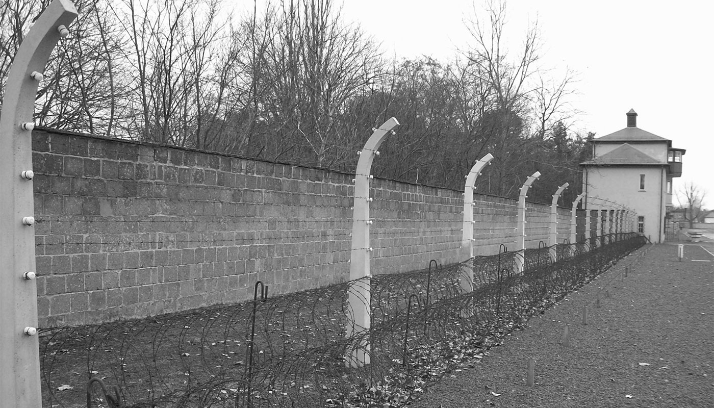 Barbed-wire fence and wall of Sachsenhausen Concentration Camp outside Berlin, Germany.