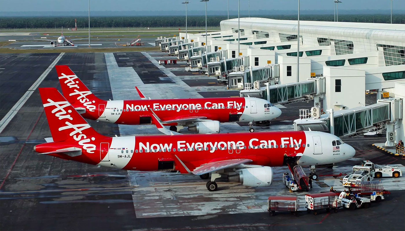 PHOTO DESCRIPTION: Two AirAsia jets at airport terminal, with a livery that says on the side of the plane, 'Now everyone can fly'.