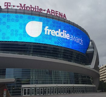 PHOTO DESCRIPTION: Facade of the T-Mobile Arena, with the Freddie Awards logo displayed on the large external video board.