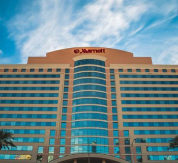 PHOTO DESCRIPTION: Front facade of the Las Vegas Marriott Hotel, set against a blue sky with white clouds.
