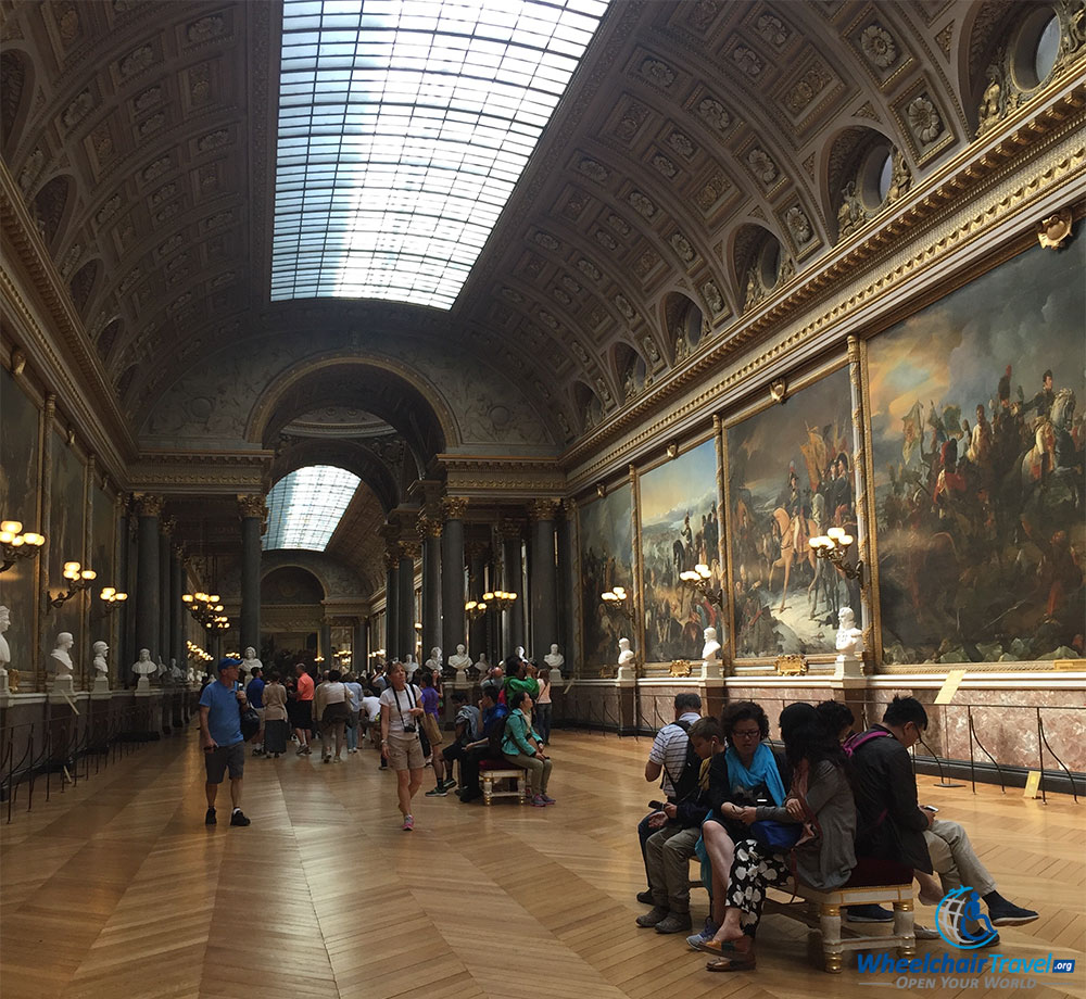 PHOTO DESCRIPTION: A long hall with a partially glass ceiling, with massive paintings on either side.