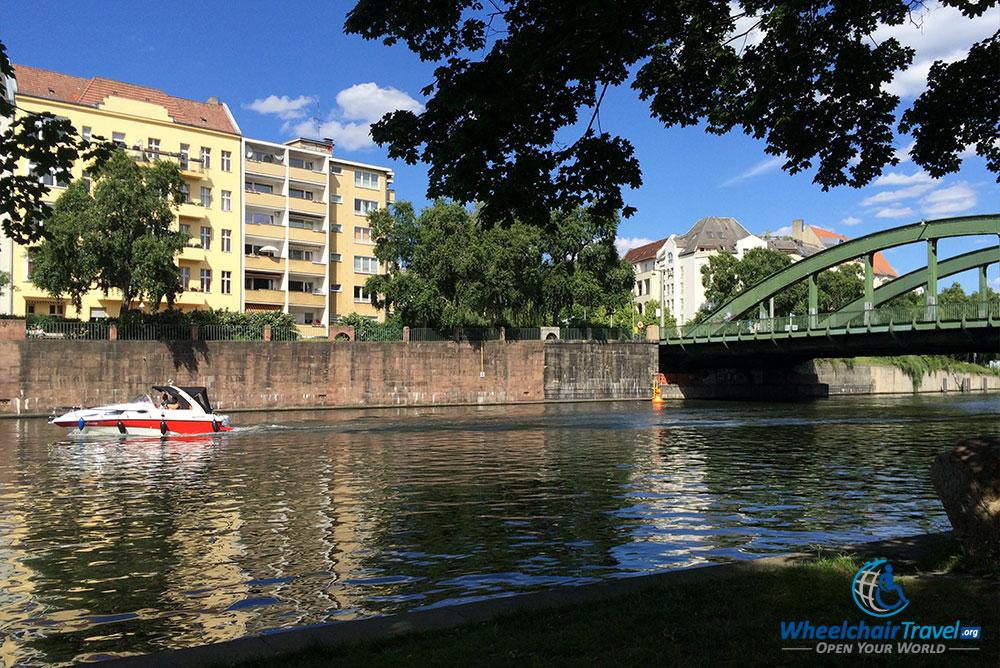 PHOTO DESCRIPTION: Boat passing under bridge that crosses a river adjacent to the palace park.