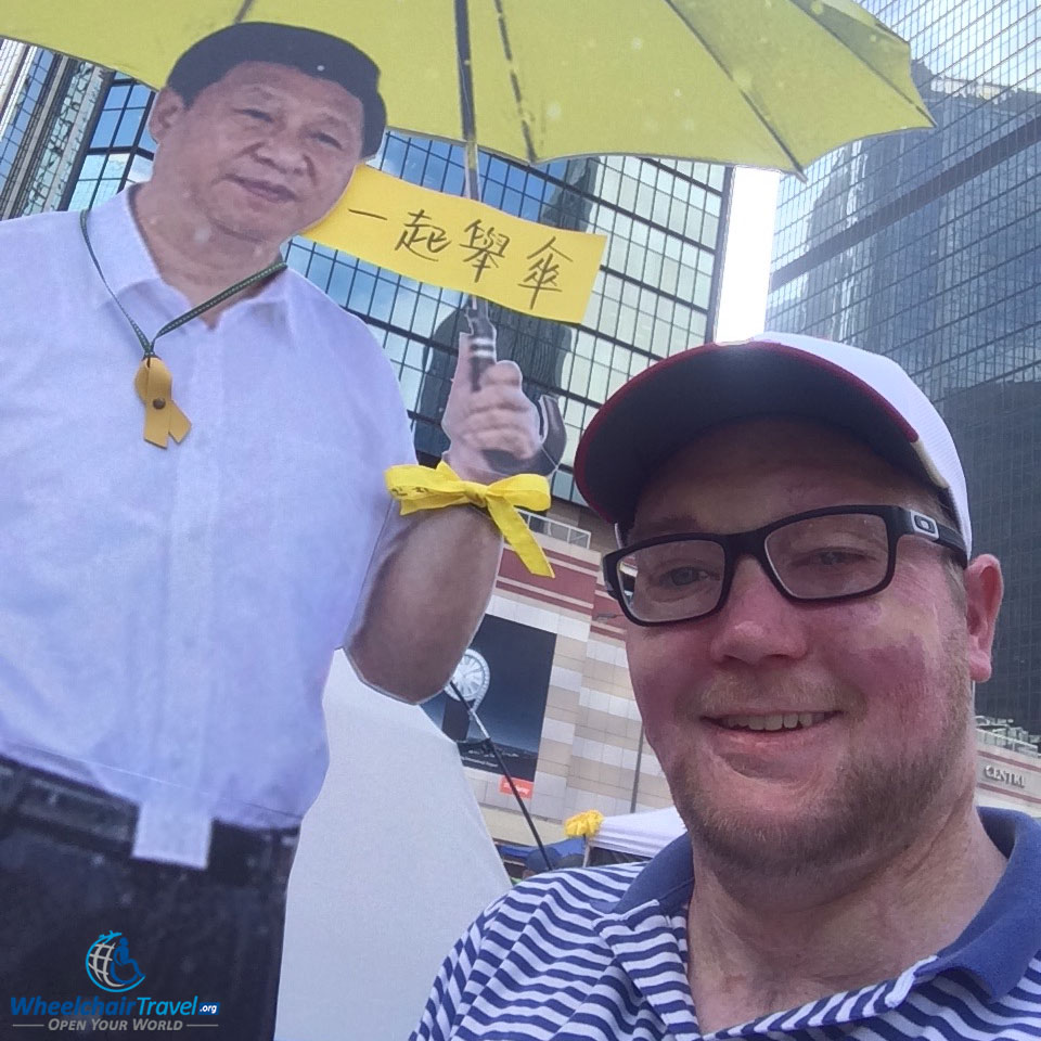 PHOTO DESCRIPTION: Selfie with a cardboard cutout of Chinese President Xi Jinping, holding a yellow umbrella.