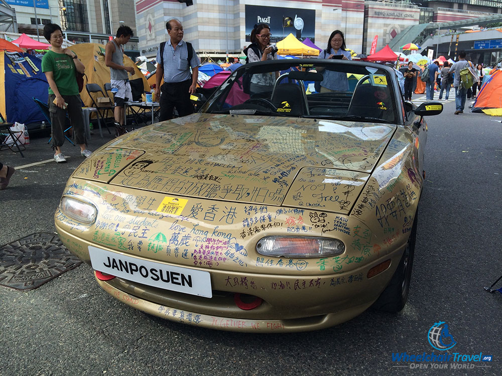 PHOTO DESCRIPTION: Convertible car covered with graffiti messages.