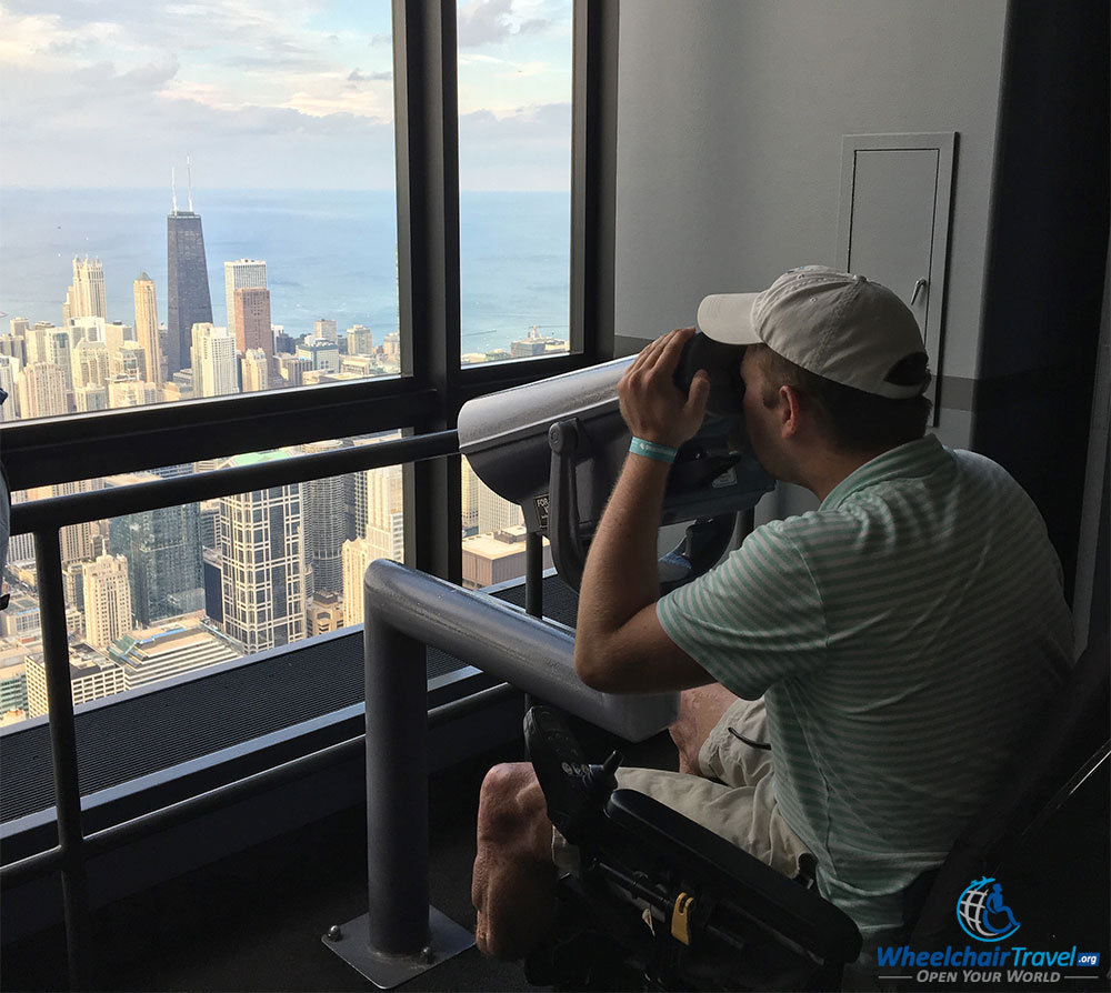 PHOTO: John looking through a wheelchair accessible telescope at Skydeck Chicago Willis Tower.