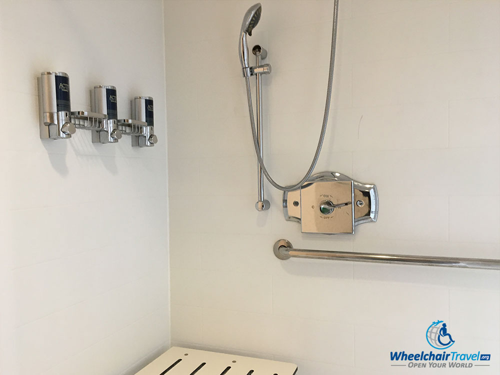 Soap dispensers attached to the wall behind the shower seat