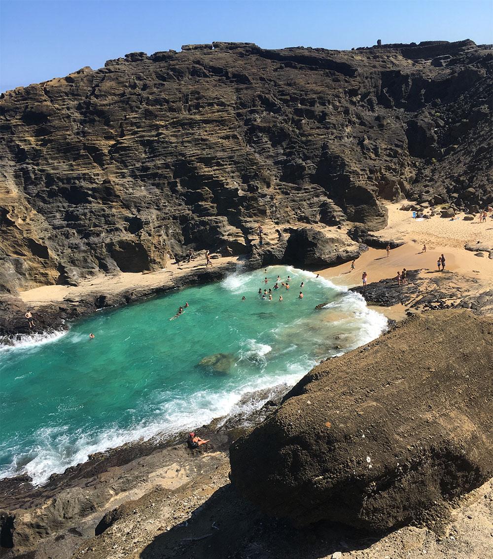 A hawaii beach between two rocky cliffs.