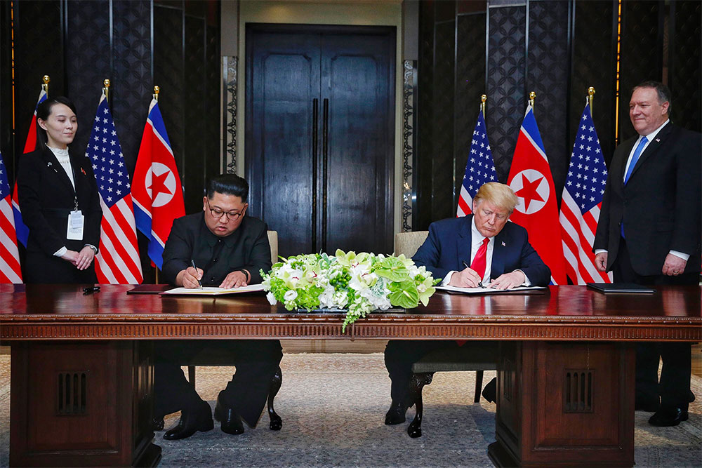 President Donald Trump and Chairman Kim Jong-un sign a bilateral agreement in Singapore. | Photo courtesy NBC News.
