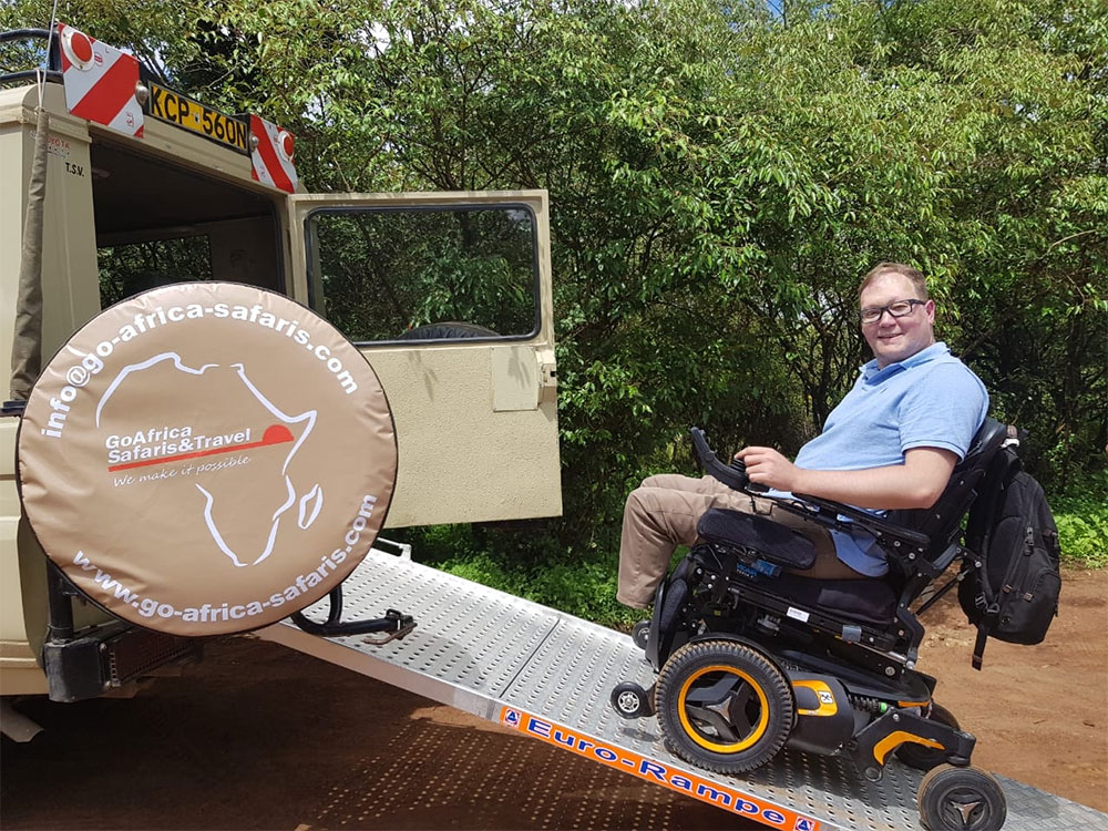 Wheelchair ascending ramp into Land Cruiser on safari.