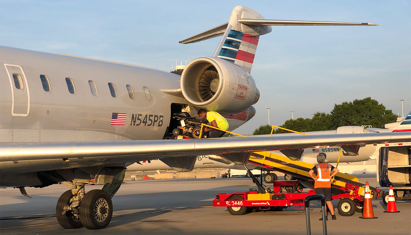 Wheelchair being loaded into cargo hold of American Airlines airplane.