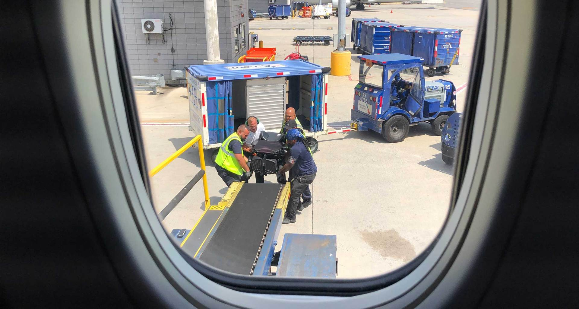Airline staff loading wheelchair on airplane.