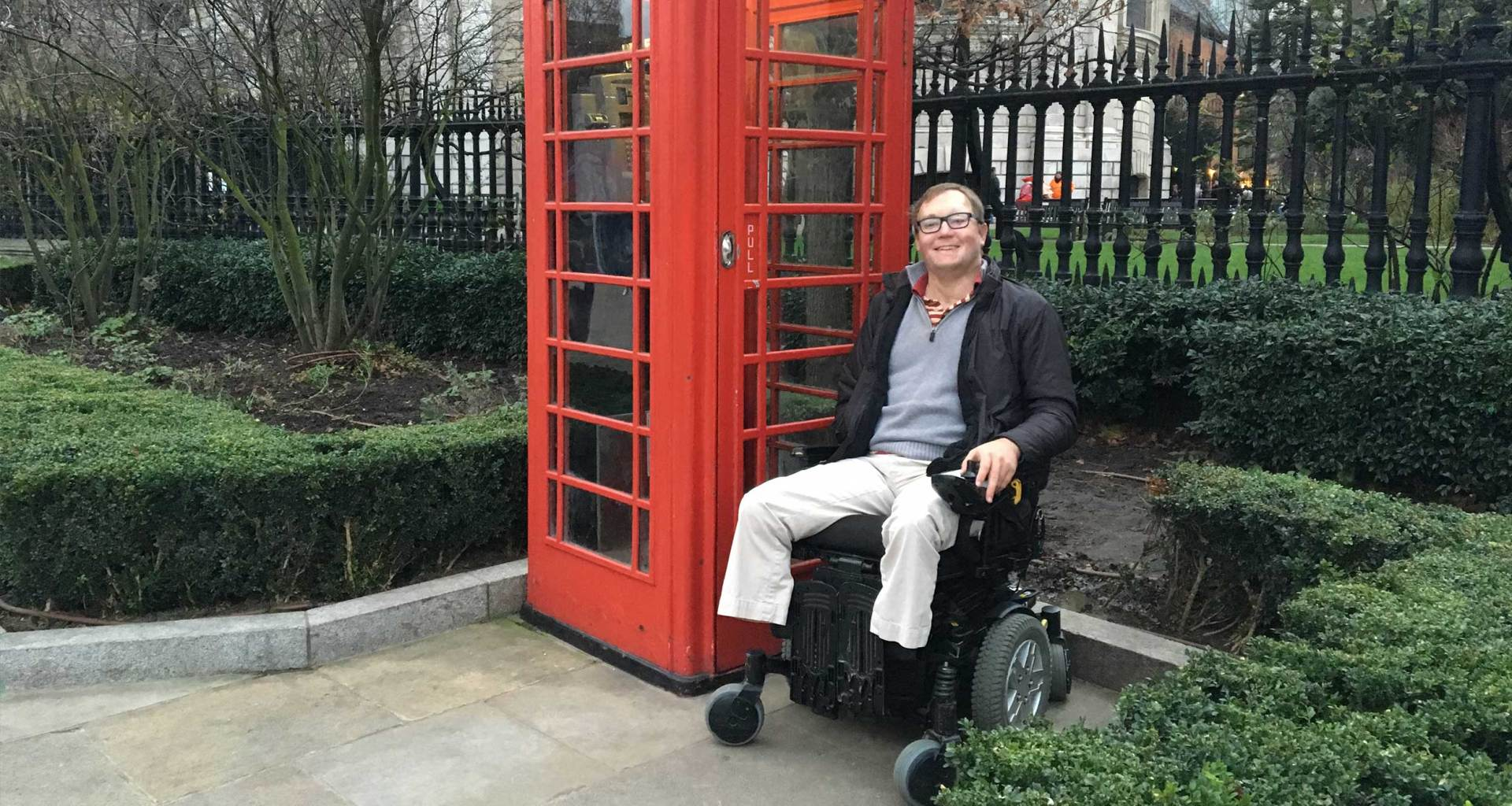 Wheelchair user next to red telephone booth in London.