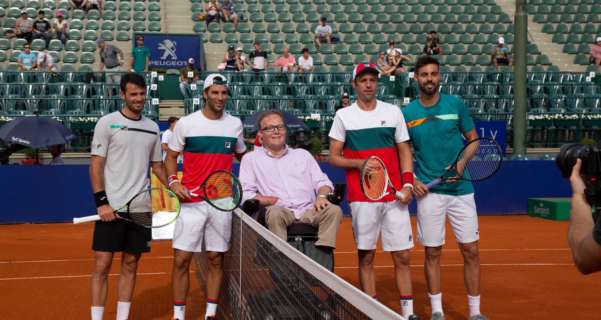 Wheelchair user at the net with 2020 Argentina Open Doubles finalists.